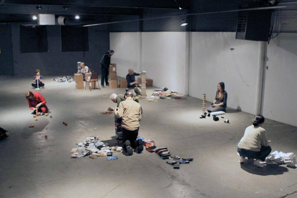 12. Stacking performance, 2013 duration 60 min. The space is empty. The whole action takes place between 8 and 9 p.m. At 8 p.m. the stackers bring in their items and pile it on the floor, each choosing their own spot near a light.