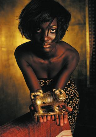 8 KOLUMNENTITEL Model holding the golden lion, a major piece from the collection. opened in 2001. This was a significant event in bringing back cultural artefacts to the continent of their origin.