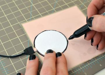 Cut out the circle with sharp scissors and then peel away the plastic overlay.