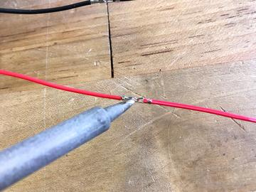 heat shrink tubing Slide another piece of heat shrink tubing over each wire, then