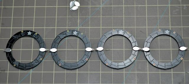 Build it! Lay out four NeoPixel rings on a gridded surface like a cutting mat. Glue on your metal jewelry findings as shown with E6000 craft adhesive and let dry overnight.