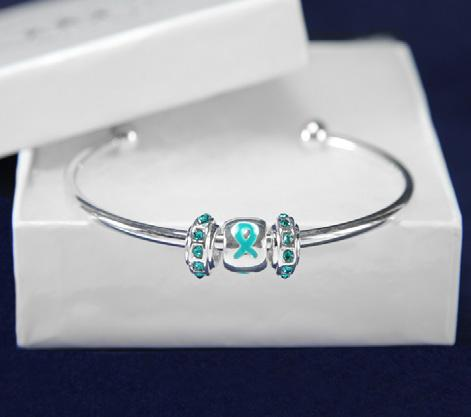 A flexible bangle bracelet that has the words Mother, Daughter, Sister, Aunt, Friend with teal ribbons.