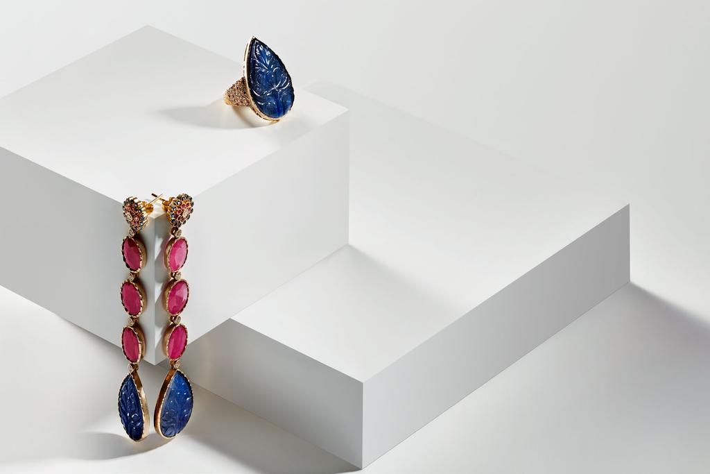 ENAMORED BY SAPPHIRE RING AN ORNATE CARVED SAPPHIRE PEAR TRACED IN THE SHIMMER OF DIAMONDS AND RUBY PAVÉ SECURE WITHIN