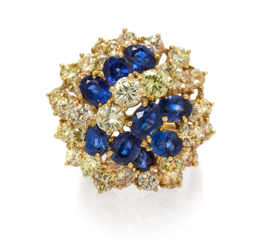 Lot 238 An 18 Karat Yellow Gold, Platinum, Colored Diamond and Sapphire Cluster Ring, Oscar Heyman Brothers, in an open wirework design, containing 33 round brilliant cut yellow diamonds (origin of