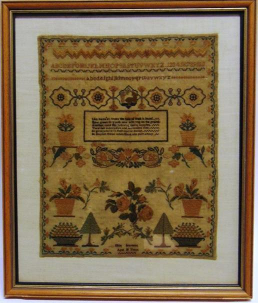 304 A NEEDLEWORK SAMPLER with verse, alphabet and floral designs, worked by Ellen Seamans, aged 10 years, 40cm x 33cm.