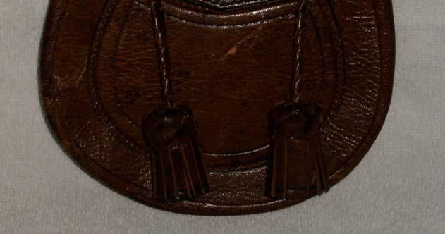 I chose to stitch it as a flat seam with the edges showing and then carefully cover the rough edges of the leather with a thin strip of leather similar to what was done at the