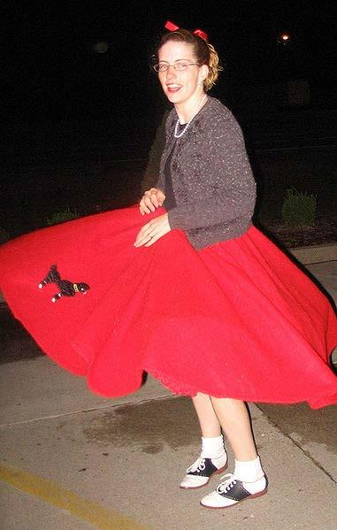 Poodle Skirt A woman twirling her poodle skirt A poodle skirt is a wide swing felt skirt of a solid bold color (often pink and powder blue) displaying a design appliquéd or transferred to the fabric.