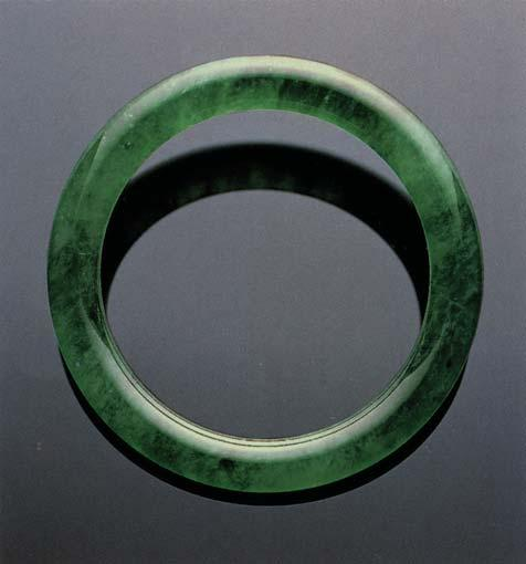 Traditionally, when fine jadeite cabochons are mounted in jewelry, they are backed by metal with a small hole in the center.