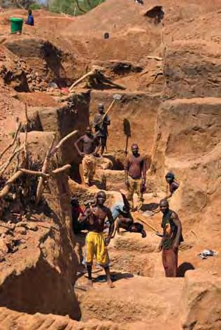 Working in small groups, they use picks and shovels to dig through the laterite overburden in search of the gem-bearing layer. Photo by B. M. Laurs. Figure 13.