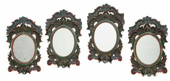 160 160 a set of four north German green and red painted oval mirrors, each carved with c-scrolls, openwork rocailles and two brass bracket arms.