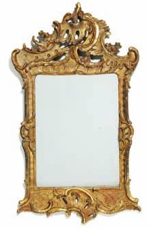 195 195 a north German rococo giltwood mirror, carved with openwork c-scrolls, rocailles and flower heads. Mid 18th century. H. 90 cm. W. 53 cm.