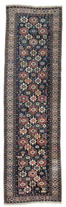 309 an antique Kuba-shirvan blossom runner, caucasus. all over design of staggered stylised flower heads on a blue field with human figures, jugs and star motifs surrounded by cufic main border.