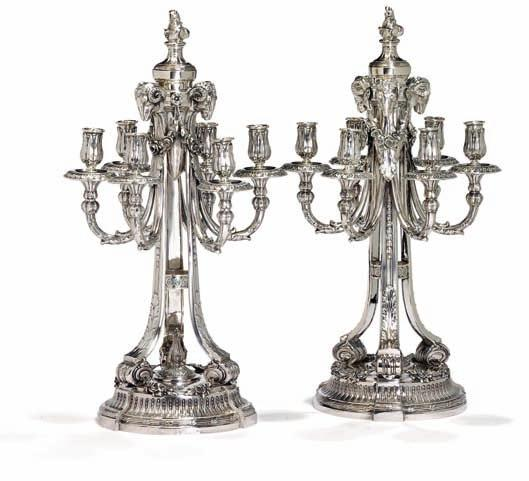 382 382 a pair of German silver six-light candelabra, cast with ram heads, garlands and foliage, threefold stem on circular base.