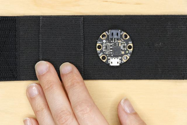 Place the pocket on the wrist band next to where the Gemma M0 will go, and try to position it so that the battery will sit flat against