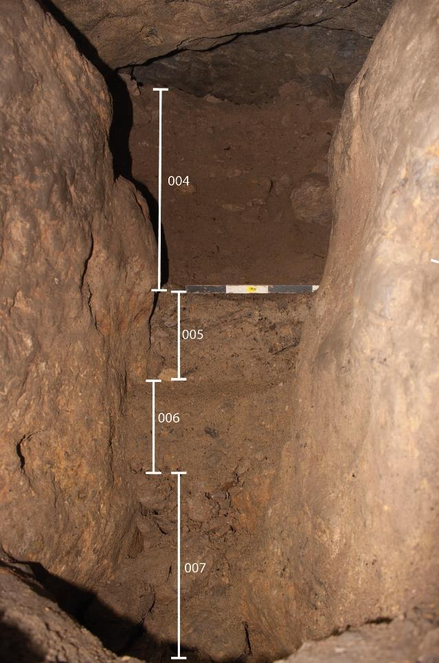 The section was cleaned revealing a faint line on the side wall - the compacted surface of the original bronze age infill. This line can be seen just to the left of the scale in figure 6.