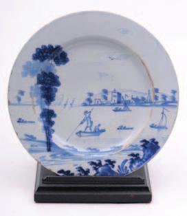 An English, probably Bristol, delft charger painted in blue with three cranes in a naive garden