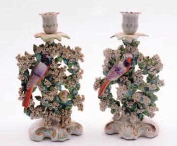 A pair of Derby porcelain birds in branches candlesticks each modelled with a pair of birds amidst a flowering bocage below a single sconce and drip pan, on a scrolling base, 24 cm high, patch marks,