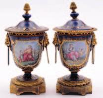 A pair of French porcelain and gilt metal mounted urns and covers in the Sevres manner enamelled with a figure and child in a landscape and verso with a songbird in a garden setting