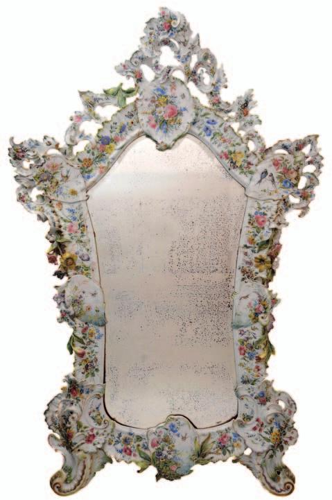 618. A large Nove faience mirror of cartouche form, constructed from ten pierced and scrolling sections each painted with bouquets
