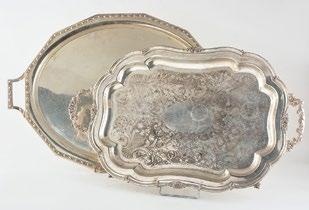 Silver plated tray resting on four clawed feet with chiseled floral decor.