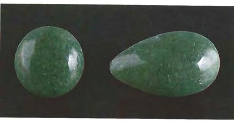 Figure 9. These jadeite cabochons (15.92 and 18.44 ct) were cut from material mined in the Sajany Moru~tains of the Russian Federation.