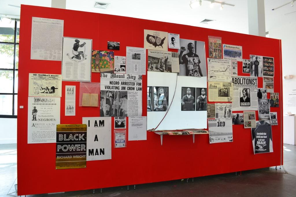 Across from these photographic portraits is an installation called Perceptions consisting of pinned vintage magazines, newspaper articles, reproductions of posters, political ads from the 1860 s, and