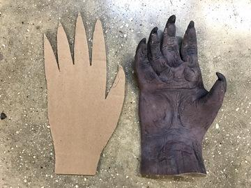If your gloves are already very stiff and springy, skip this first step. Cut a rectangle of cardboard approximately the same dimensions of your glove.