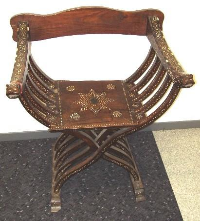Furniture 2005.731 Chair Wood, bone / hand-crafted Large ornate wooden chair, flat back panel (new) and seat, perpendicular arms with five symmetrical curved ribs crossing under chair to form legs.