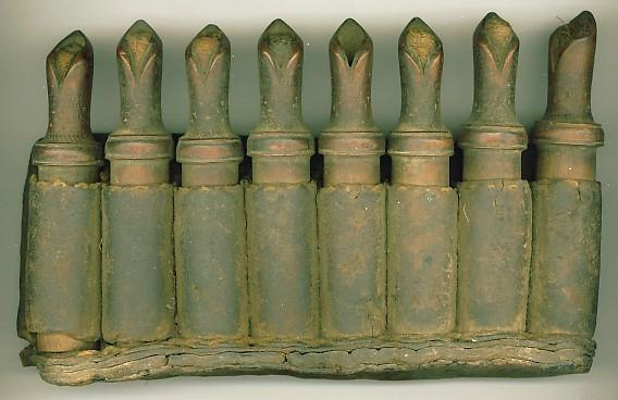 Weaponry 2005.749 Powder bottle Wood, leather / hand-crafted Afghanistan / 19th C. Set of eight small cylindrical wooden powder bottles with cloth stoppers fitted into a leather holder.