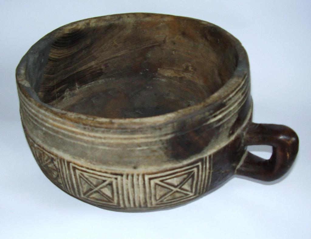 Vessel 2005.739 Bowl Wood / hand-crafted Carved flat-bottomed bowl, with slightly curved straight sides, on small flat base. Four concentric incised lines around outer rim.