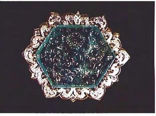 Figure 4. Brooch with carved slice from emerald crystal as center stone. Emerald measures 9.1 m m x 50.8 mm x 40.35 mm. thin section of a crystal for personal adornment.