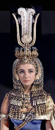 Cleopatra s Headdress The headdress was topped by a crown, based on the one on the bas-relief at Denderah, formed by a circle of cobras and the sun disk and the two feathers associated with the