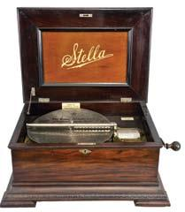 5 inch music box with 10 discs, oak case with stepped ogee base and locking drawer, rope molding, stepped, molded lid, the inside with music-themed