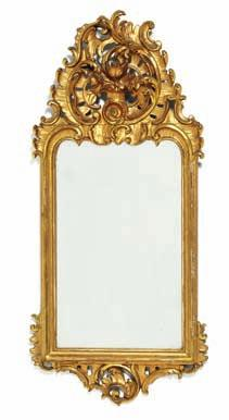 190 a north German rococo giltwood mirror with openwork c-scrolls and rocaille carvings. Mid 18th century. H. 82 cm. W. 37 cm.