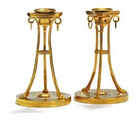 269 a pair of french empire gilt bronze candlesticks, each with tapering angular stem on paw feet, round arched bases. early 19th century. H. 26 cm.